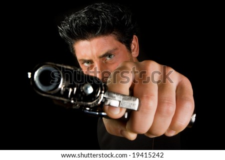 Dark man pointing a gun looking at the camera