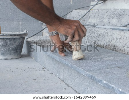 Dark marble tiles for flooring the stairs Is for fixing stairs and fixing cement work, marble work. Workers are using the hammer handle to knock the tiles in the same plane.