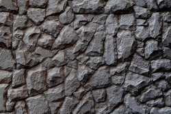 Dark masonry wall texture. Black stones and rocks of different shape, gray background