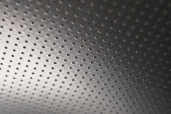 Dark metal wallpaper or background. Perforated aluminum surface with many holes, hanging from above like a ceiling. Perforation rows go into the distance and form perspective