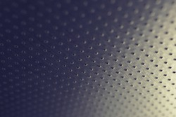 Dark metallic wallpaper. Tinted blue and yellow background. Perforated aluminum surface with many holes, hanging from above like a ceiling. Perforation rows go into the distance and form perspective