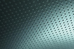 Dark metallic wallpaper. Tinted blue-green background. Perforated aluminum surface with many holes, hanging from above like a ceiling. Perforation rows go into the distance and form perspective