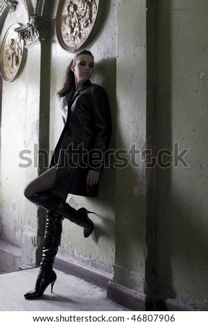 dark model wearing a leather coat and boots in an old fashion main entrance of old house