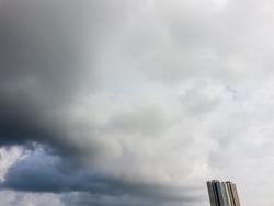Dark monsoon clouds in the sky above a high rise skyscraper in suburban Mumbai.