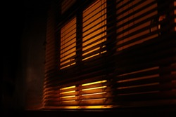 Dark, moody atmosphere set by yellow light softly piercing through the blinds. The shutters create a lovely contrast between light and shadow.Also a concept of mafia, fear, kidnapping, sleep, sunlight
