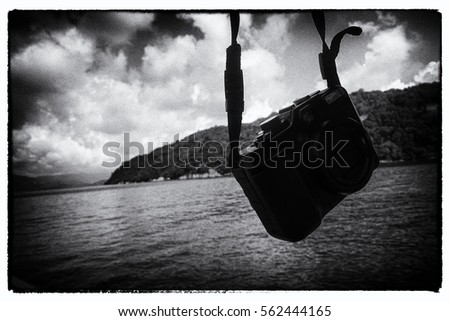 Dark moody black and white image of a camera hanging by a strap in front of a hilly coastline with calm sea on a cloudy day #562444165