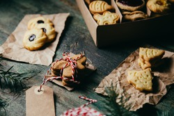 Dark moody gingerbread cookies for Christmas in a small paper box decorated on rustic green table.
