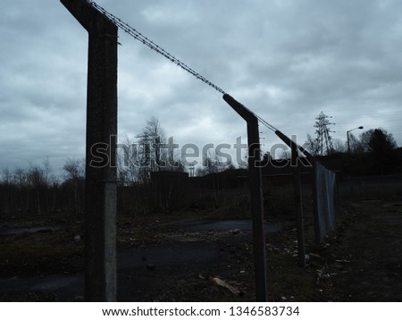 dark moody posts and barbed wire #1346583734