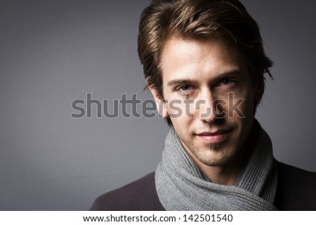 Dark moody studio Portrait of an attractive man looking out of the shadows with an enigmatic expression