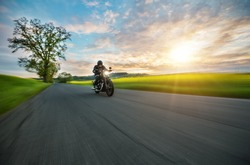 Dark motor-biker riding high power motorbike in nature with beautiful sunset light. Travel and transportation. Freedom of motorbike riding