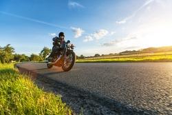 Dark motorbiker riding high power motorbike in nature with beautiful sunset light. Travel and transportation. Freedom of motorbike riding