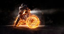 Dark motorbiker staying on burning motorcycle at night. Dark art wallpaper photo of chopper motorbike.