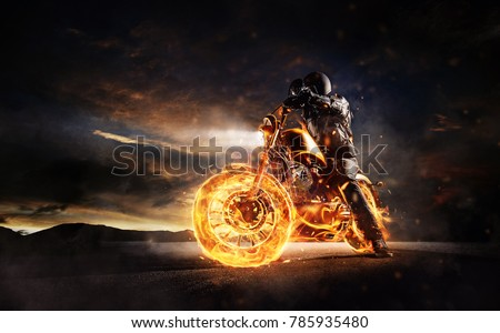 Dark motorbiker staying on burning motorcycle in sunset light. Dark art wallpaper photo of chopper motorbike. Very high resolution image