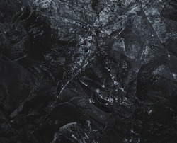 Dark Mountain. Black marble. Rock background. Rough structure. Rock surface with cracks.  Abstract texture. Stone wall. Rock texture. Stone background. Stone mineral texture. Rock pile background