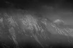 Dark mountainscape on a cloudy evening in High Tatra Mountains, Poland. Clouds rising over the peaks and crags. Selective focus on the rocks, blurred background.
