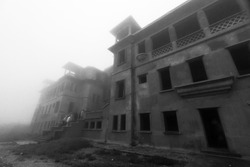 Dark mystic atmosphere of abandoned Bokor Palace Hotel in foggy. A group of tourists walks through the main entrance to Bokor casino hotel. Borkor Mountain, Kampot, Cambodia. Monochrome. Soft focus.