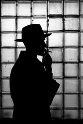 dark mystical silhouette of a man in a hat Smoking a cigarette at night in retro Noir style