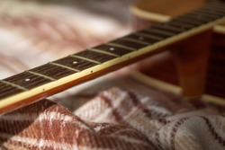 dark neck guitar without strings with frets of light wood on a woolly brown warm cage plaid