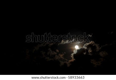 Dark night sky with the moon surrounded by highlighted clouds.