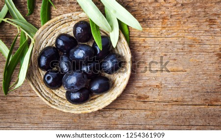 Dark olives with leaves on a wooden table #1254361909