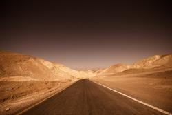 Dark, ominous road leading through desert of badlands Death Valley National Park