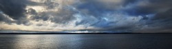 Dark panoramic scenery of the forest lake during the storm. Nature of Scandinavia. Dramatic glowing clouds, waves and water splashes. Epic cloudscape. Autumn landscape. Environment, ecology, seasons