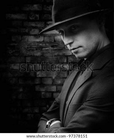 Dark photo of a Man with hat standing against brickwall background