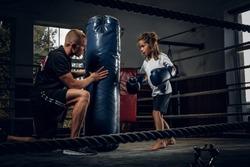 Dark photo shoot of kids training with big punching bag at boxing studio.