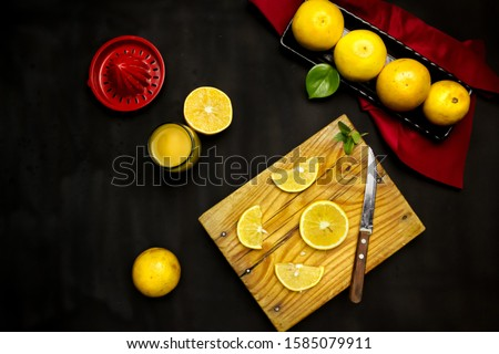 dark photograph of food in zenithal view of some oranges, some whole other slices, a red juicer, a knife and a glass with juice
