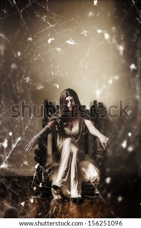 Dark portrait of a possessed demon woman  seated in haunted house in vintage fashion with spiderweb. Devil is in the details