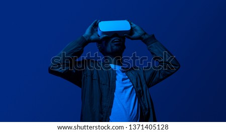 Dark portrait of amazed black man wearing VR helmet and looking up and expressing Wow reaction
