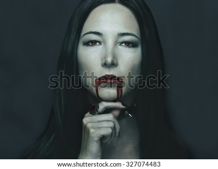 Dark portrait of beautiful young woman with vampire halloween make-up. Halloween or horror theme