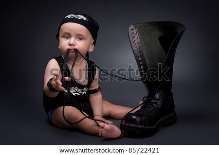 dark portrait of  rocker-baby on a black background - stock photo