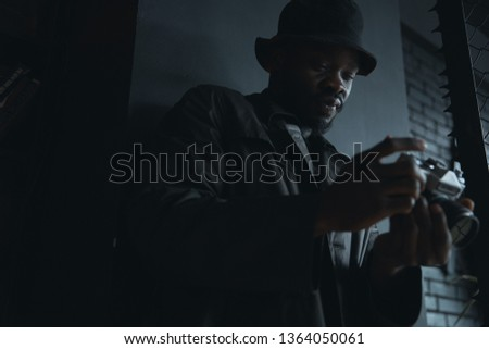 e17d163eca5 Dark portrait of young fashionable man in black trench coat and bucket hat