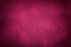 Dark purple matte background of suede fabric, closeup. Velvet texture of seamless wine leather. Felt material macro with vignette.