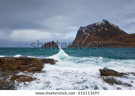 Dark rainy clouds over the mountains of Lofoten islands in winter #616113695