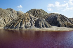 Dark red, acid, industrial lake on the background of the clay hills and blue sky with clouds.