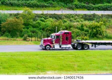 Dark red big rig bonnet classic American semi truck with vertical pipes transporting empty flat bed semi trailer driving on highway to warehouse for pick up next commercial load for delivery #1340017436