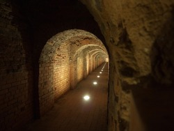 Dark red brick old fortress underpass tunnel illuminated with spotlights, St Petersburg, Russia