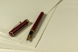 Dark red fountain pen with gold nib and loose cap on a number of sheets of cream colored paper as background photo