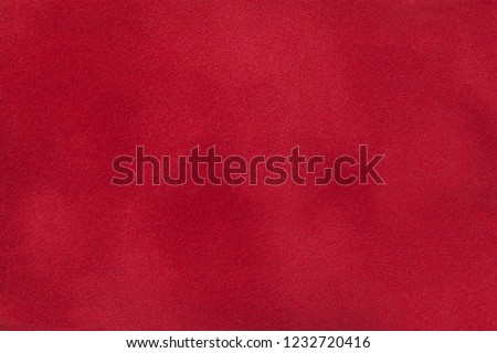 Dark red matte background of suede fabric, closeup. Velvet texture of seamless wine leather. Felt material macro.