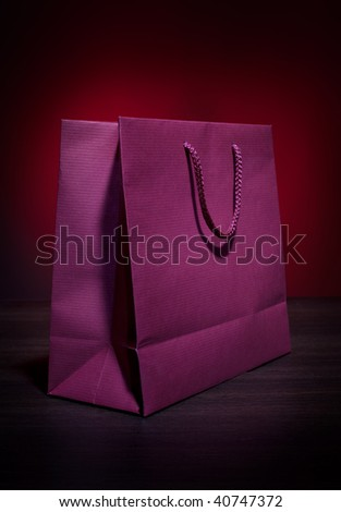 Dark red paper bag on dark table top - stock photo
