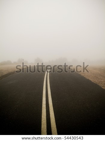 Dark road with double lines disappears into very thick fog