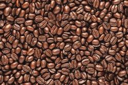 Dark roast coffee beans background, top view