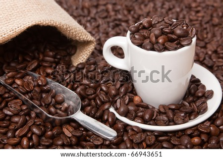 Dark roasted coffee beans with a burlap sack, metal scoop and espresso cup.