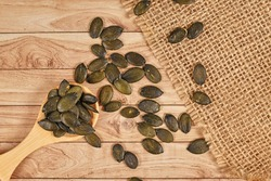 Dark roasted pumpkin seeds without husks on wooden table