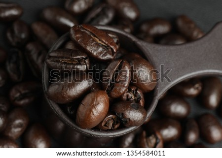 Dark roasted robusta coffee beans on a measuring spoon #1354584011