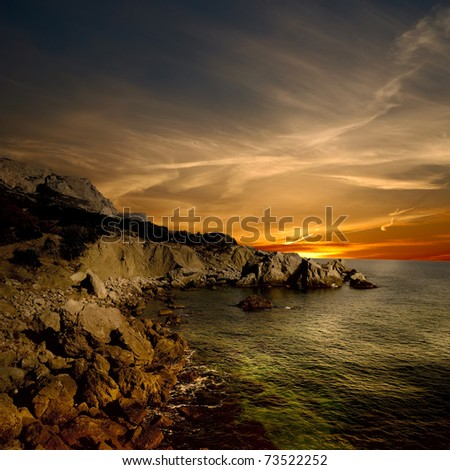 dark rock and sea coast at sunset time