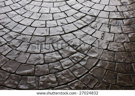 Dark rustic floor paving stones laid in a rounded pattern
