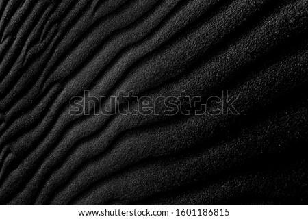 Dark Sand. Black sand waves as background. Dark on Tenerife. Volcanic sand. Texture of black volcanic soil for background. Black Sand beach macro photography. Texture of black volcanic stone. Photo stock ©
